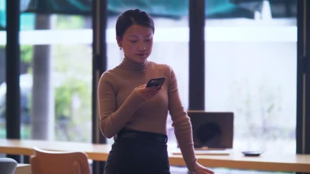 Junge asiatische Geschäftsfrau benutzt Handy im Büro
