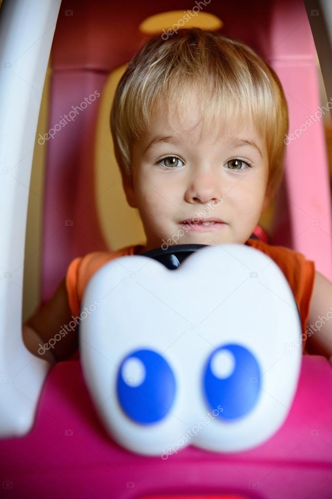 Smiling boy in a toy car