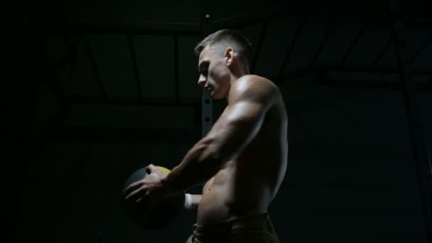 Fitness-Mann beim Training im Fitnessstudio mit Fitness-Ball Stretching Muskeln. Workout Fitness und Bodybuilding gesundes Konzept Hintergrund. Kaukasischer Bodybuilder macht Bauchmuskelübungen im Fitnessstudio
