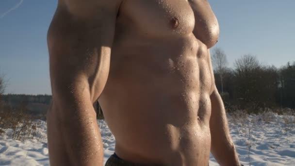 fitness muž dýchá v zimě venku. Flexní svaly. Sport, zdraví a kalení koncepce