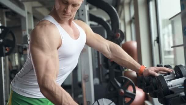 dobře vypadající fit muž zahřívá zápěstí a svaly v tělocvičně před cvičením stojící u okna venku. Koncept kulturistiky, fitness a zdravotní péče.