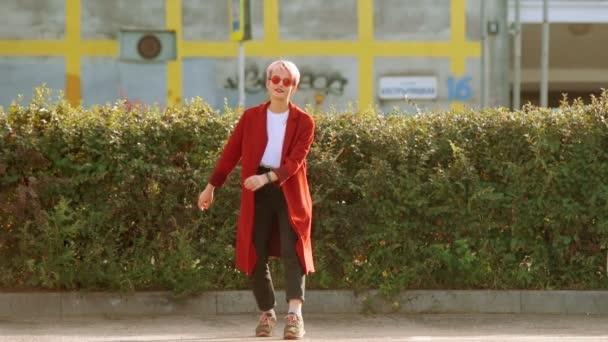 Coole Hipster-Aukasierin mit rotem Mantel und roter Brille tanzt auf der Straße der Stadt