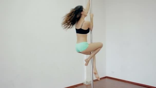 Široký záběr mladá dívka tančí poledance v bílé místnosti