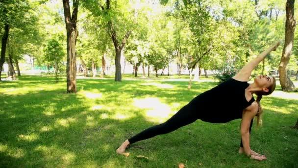 Široký záběr mladá žena dělá jógu v parku