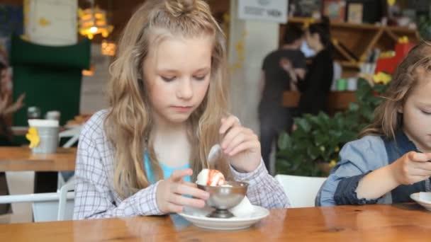 dvě dívky v kavárně jíst zmrzlinu se sirupem