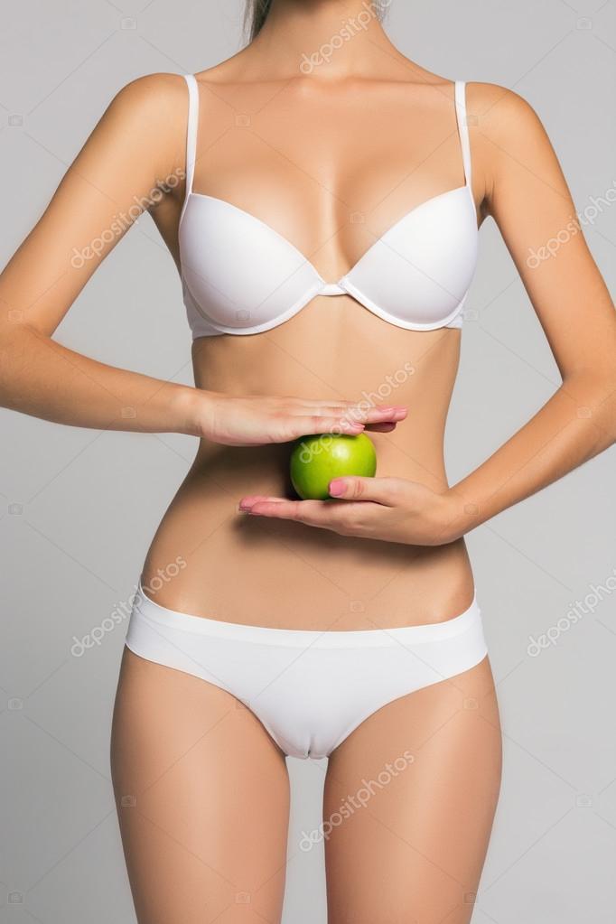 A képet egy nő gazdaság fit hasára előtt egy zöld alma — Fotó szerzőtől  Sane4eG e59efa165d