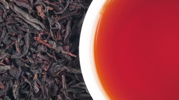 Background and texture of rotating black tea leaves and a cup of tea. View from above.