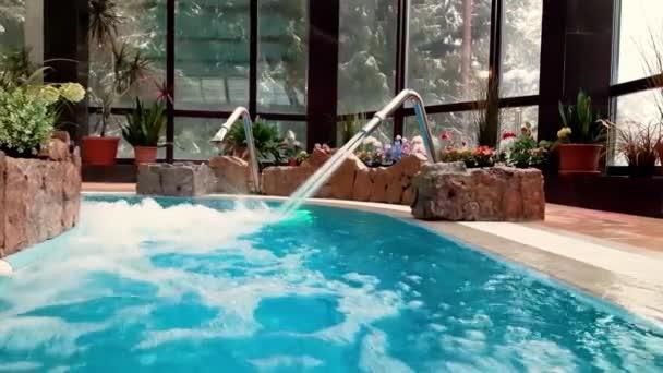 Prázdný krytý bazén s vodopádem pro masáže.