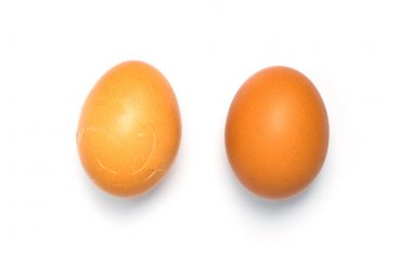 Couple of Eggs isolated on white background. One of them is cracked.
