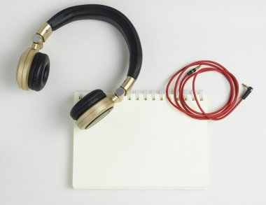 Blank note book binder with Golden music headphone.