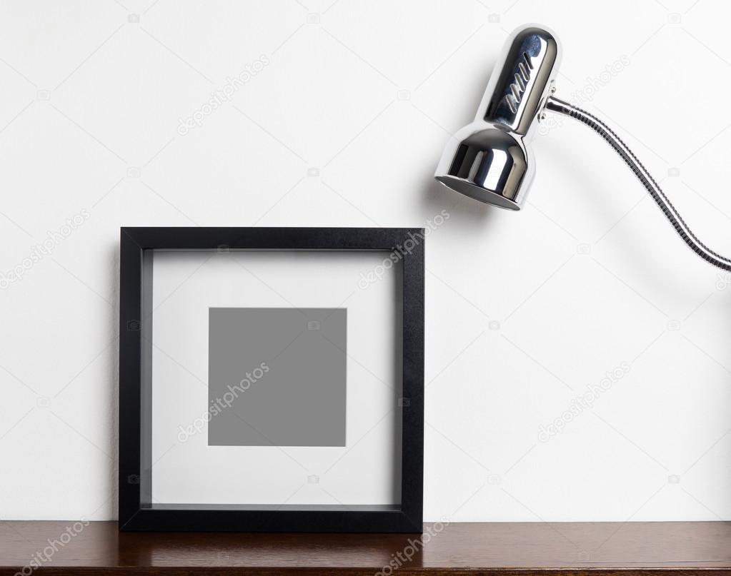 dicke schwarze bilderrahmen mit lampe auf regal — stockfoto