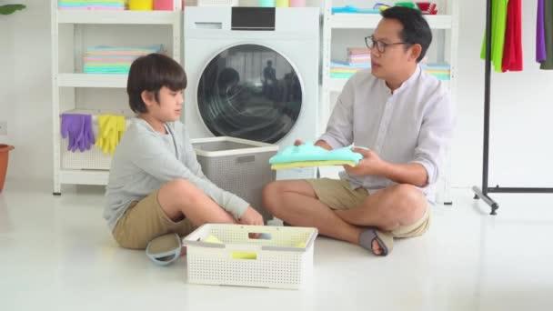 Otec a syn společně připravují oblečení na pračku pro koncepci práce v rodinném domě.