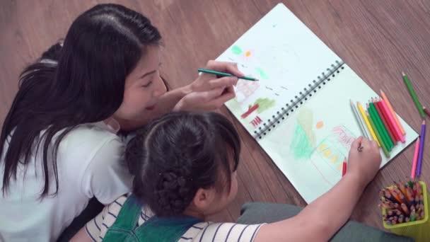 Matka pomáhá své dceři dělat domácí práce a omalovánky na. podlaha pro výtvarnou výchovu a tvůrčí činnost.