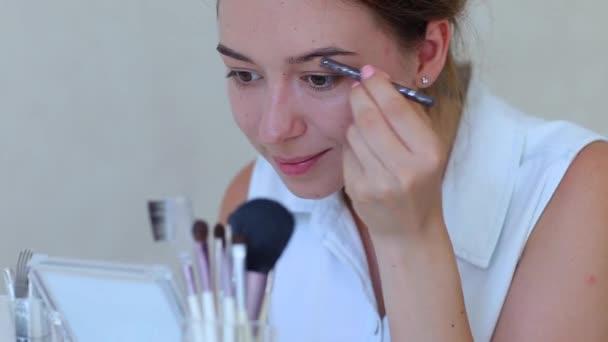 Brush make up girls hand in white room doing makeup shadows