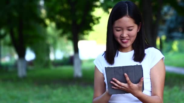 Young beautiful Asian uses a tablet waves and look to camera in
