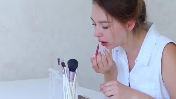 Mladé samice tvoří Rouge rty s štětec na Make-Up v rukou dívky v bílém pokoji