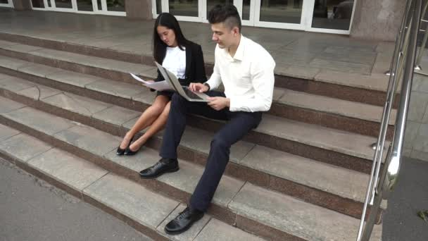 Young Asian Beautiful Business Woman Female and Caucasian Male Use Documents, Laptop Press Keyboard Sit on Office Building Stairs