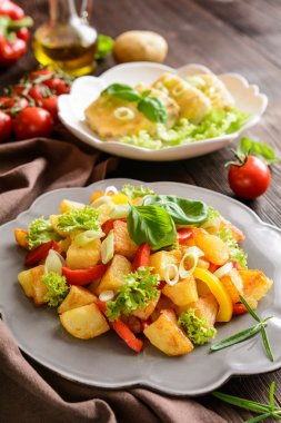 Fried potato salad with lettuce, pepper, onion and baked fish fillets covered with cheese