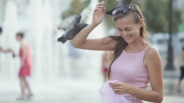 Attractive young woman feeding pigeons in the park
