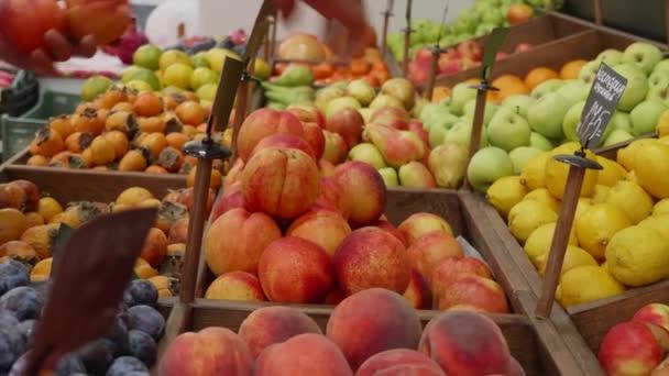 Egy élelmiszerbolti munkás közeli kezei organikus gyümölcsöket rendeznek a boltok polcain..