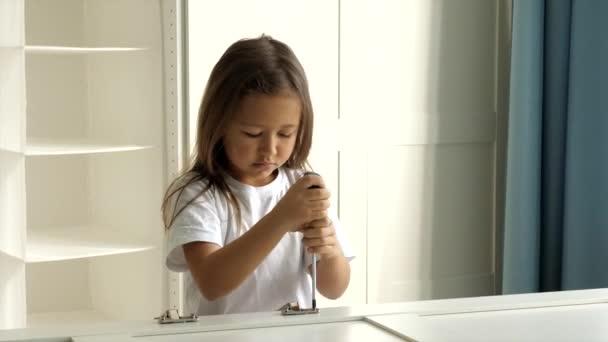 Ein kleines Mädchen montiert die Scharniere an den Schranktüren