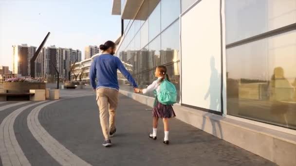 Apa a kislányával egyenruhában iskolába megy reggel.