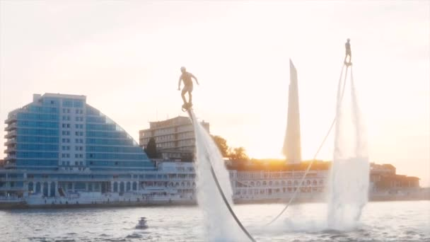 Unrecognizable flyboarders are making tricks at sunset in slow motion.