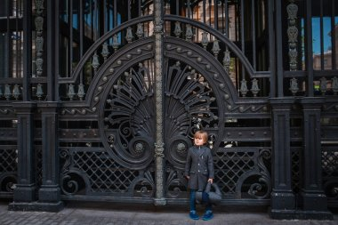 Little boy by forged gates
