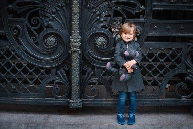 Little boy by forged gates