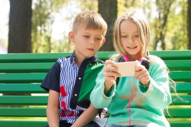 Boy and girl looking at the phone .They look very enthusiastical