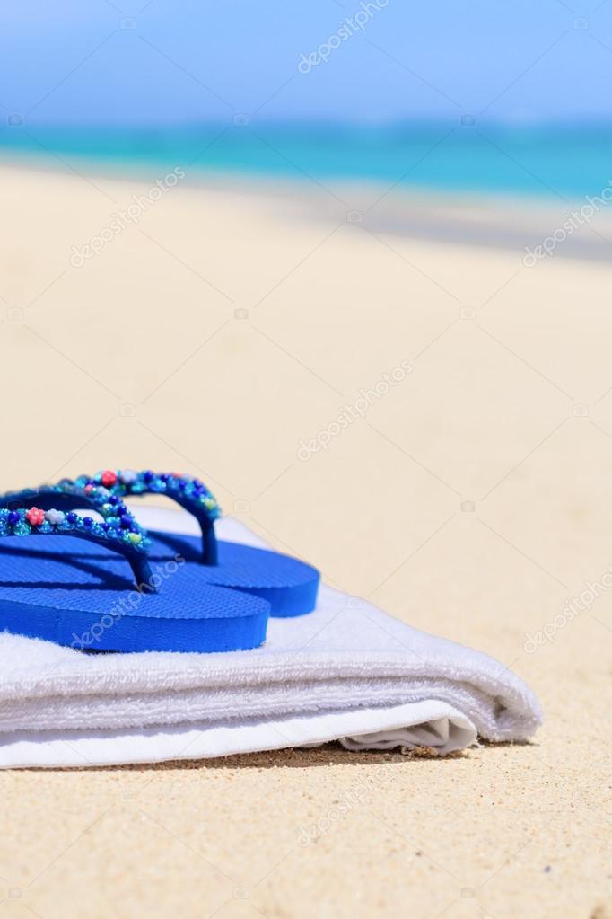 4a67ad5be759b Ein paar blaue Flip flops auf ein weißes Handtuch am Strand mit dem Meer–  Stockbild