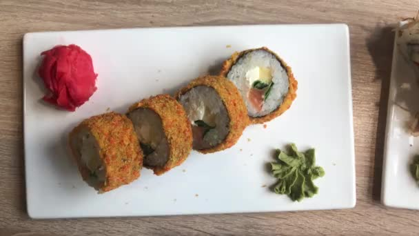 Horní pohled na japonské jídlo. Na talíři jsou rolky, zázvor, wasabi.
