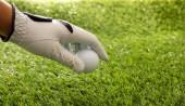 Golfový míček v rukavici, zelené hřiště na trávníku pozadí, zblízka pohled. Golfový sport a klubový koncept. Kopírovat mezeru, šablonu