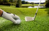 Golfové hřiště, golfový míček a klub na zeleném trávníku, modrá oblačná obloha pozadí. Golfista ruka v rukavici drží míč, zblízka pohled.