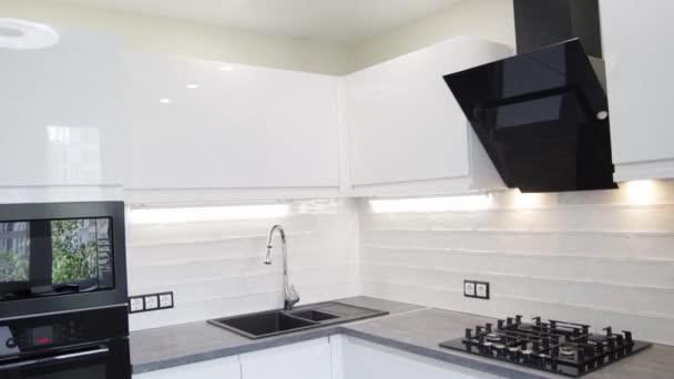 Bílý kompaktní kuchyňský interiér s vestavěnými domácími spotřebiči