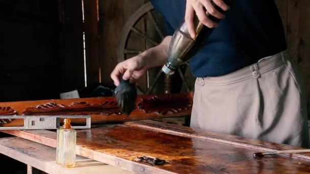 Handwerker arbeitet in einer Werkstatt mit Holz, lackiert Möbel aus Holz.