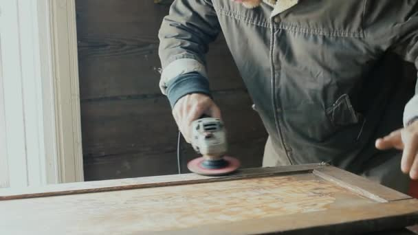 Männliche Handwerker schleifen ein Holzbrett, Schranktür mit einem elektrischen Schleifer. Restaurierung von Möbeln.