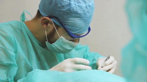 Chirurgenarzt mit Brille operiert einen Patienten im Operationssaal
