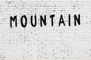 White brick wall with inscription mountain handwritten with black paint