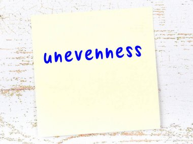Concept of reminder about unevenness. Yellow sticky sheet of paper on wooden wall with inscription