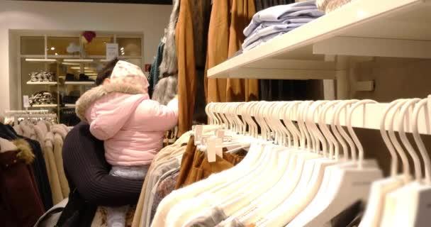 Žena s Baby volba oblečení během nakupování