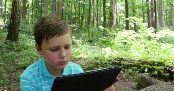 Boy With Tablet In The Forest
