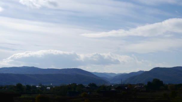 Idő telik el. felhők át a falu, a hegyek felett