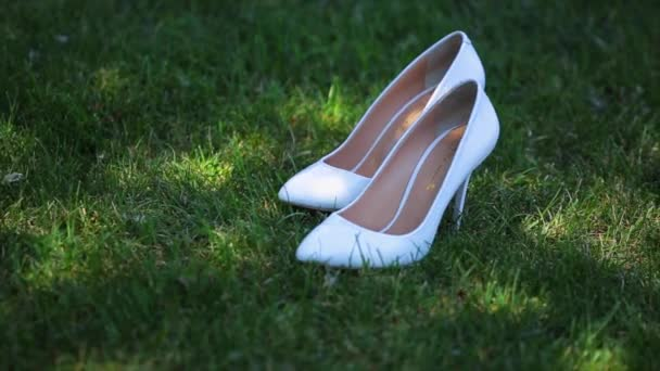 brides white wedding shoes in the grass