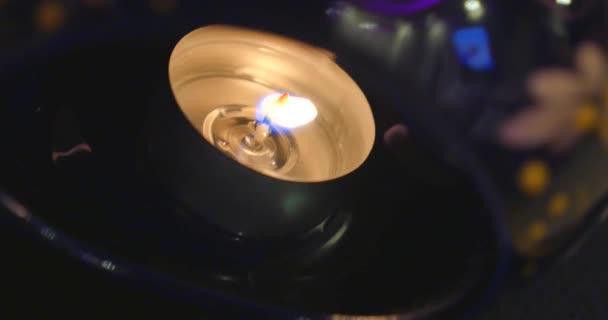 Jeden hořící tealight v temnotě, detail
