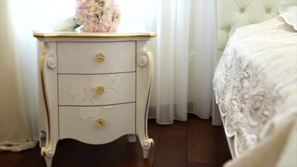 Beautiful white wedding flowers on the white vintage bedside table