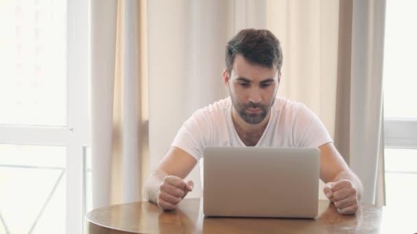 4k zpomalení videa mladého muže sedícího za stolem v kanceláři.