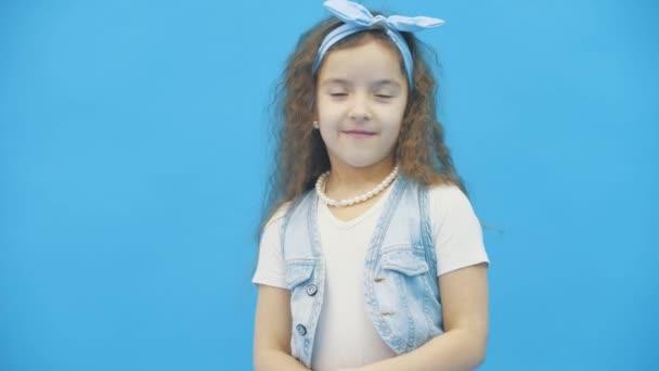 4k-Zeitlupenvideo, in dem Mädchen mit lockigem Haar über blauen Hintergrund lächeln.