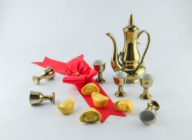 Gold ingot Red ribbon bow Gold jug Tea glass on white background