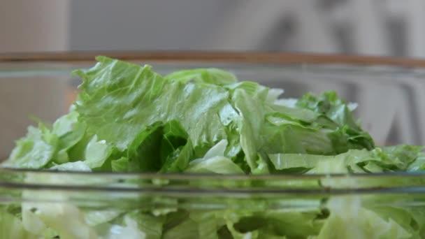 Zdravý zeleninový salát s panenským olivovým olejem. Vylévající olivový olej. Hlávkový salát, rajčata, salátová okurka. Organické bio potravin. Dieta, dieta koncept. Vegetariánské jídlo. Vegan. Zpomalené video záznam 1080 full hd